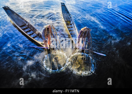 High angle view of Asian fishermen using fishing net in canoes on river