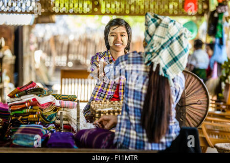 Asian teenage boy selling fabric at market - Stock Photo