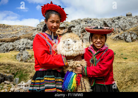 Hispanic sisters smiling with llama in rural landscape - Stock Photo