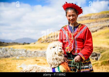 Hispanic girl walking llama in rural landscape - Stock Photo
