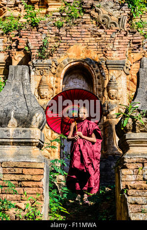 Asian monk-in-training with parasol walking on Buddhist shrine - Stock Photo