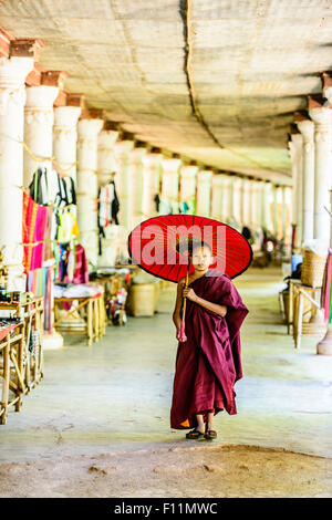 Asian monk-in-training with parasol walking in hallway - Stock Photo