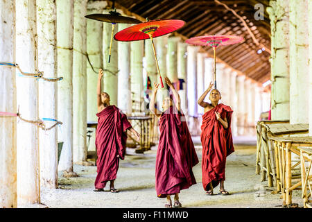 Asian monks-in-training playing with parasols in hallway - Stock Photo