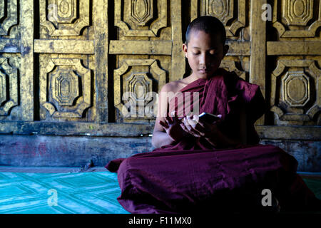 Asian monk-in-training using cell phone in temple - Stock Photo