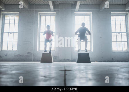 Silhouette of athletes jumping on platforms - Stock Photo