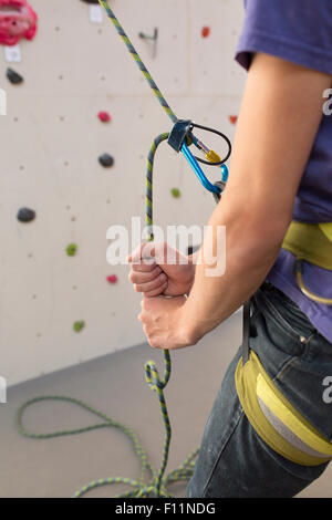Athlete tying climbing harness at rock wall in gym - Stock Photo