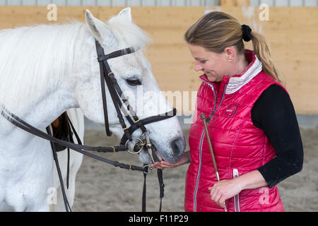 German Riding Pony Rider after riding lesson giving white pony treat - Stock Photo