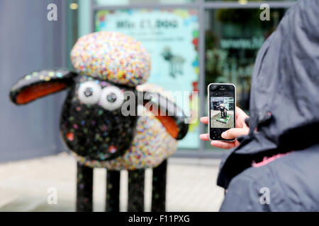 Undeterred by the rain a visitor takes a picture, with her phone, of a Shaun the Sheep character.  Bristol Shaun - Stock Photo