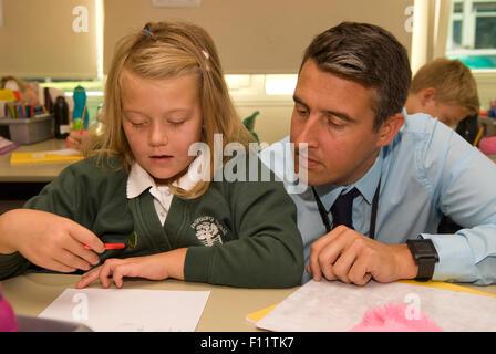Primary school teacher assisting pupil in classroom, Midlands, UK. - Stock Photo