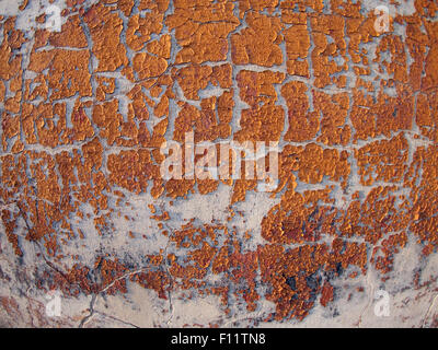 Fragment of gray concrete wall, which is covered with old, crumbling red paint - Stock Photo