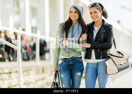 Two young beautiful women walking and shopping happily on a sunny day - Stock Photo