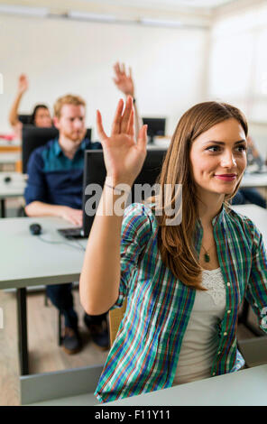 Beautiful young girl raising hand in classroom while sitting at a desk - Stock Photo