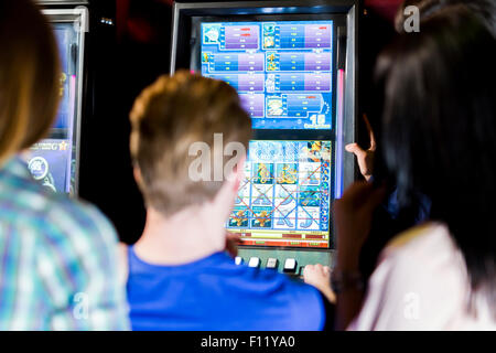 Young group of people gambling in a casino playing slot and various machines - Stock Photo