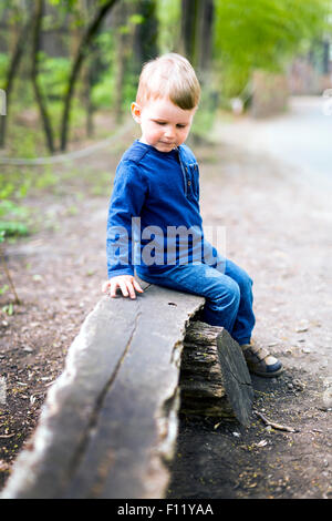 Cute little boy sitting on a wooden bench - Stock Photo