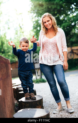 Beautiful young mother and her child holding hands outdoor - Stock Photo