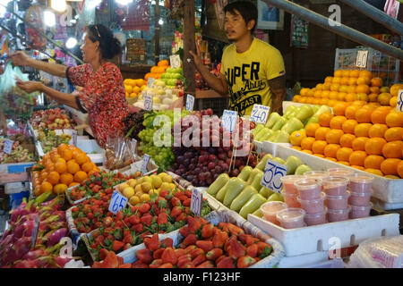 Fruit stall in a Bangkok food market with prices in Thai baht and a woman serving customers, Thailand - Stock Photo