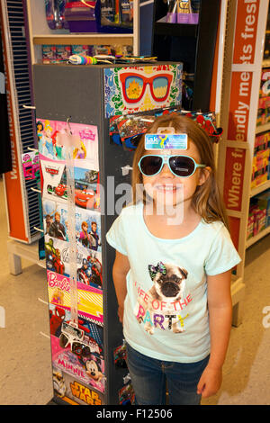 six year old girl is shopping in store for new sunglasses and having fun doing it. - Stock Photo