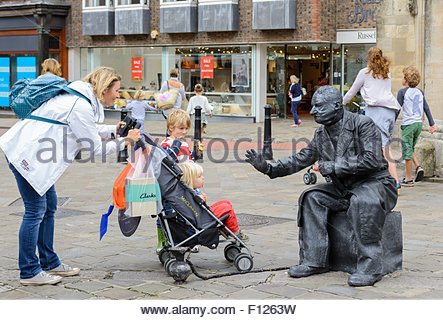 Living Statue street performer with a collection jar in a shopping centre in Chichester, West Sussex, England, UK. - Stock Photo