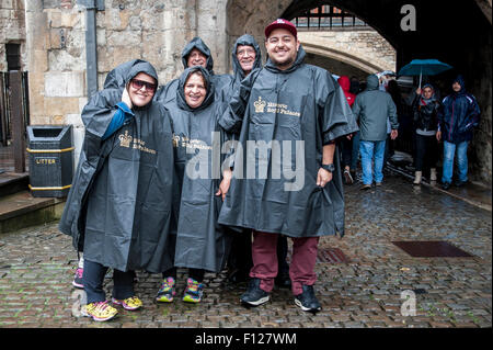 London, UK. 25 August 2015.  With the dry days of summer already a distant memory, tourists in matching ponchos - Stock Photo