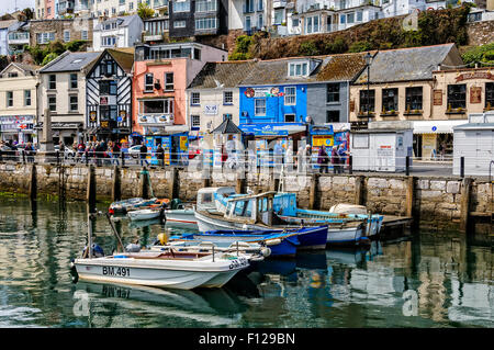Pastel coloured houses nestle above a row of attractive shops along the promenade in the picturesque harbour of - Stock Photo