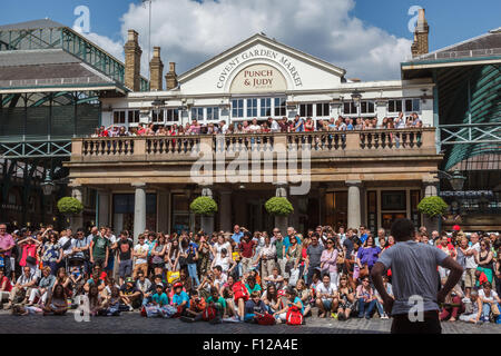 Street performer entertaining a crowd on a sunny day in London's Covent Garden piazza. - Stock Photo