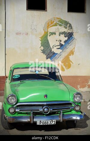 Vintage Green Ford taxi parked beneath Che Guevara mural in the parking lot in Old Havana Cuba - Stock Photo