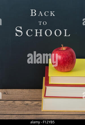 Red apple on the stack of books. Chalkboard background with Back to School text. - Stock Photo
