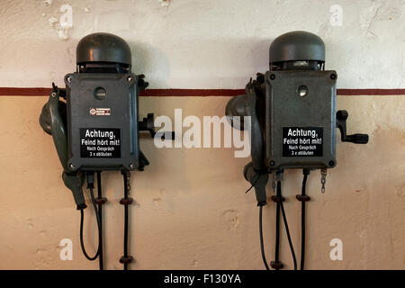 Two telephones in a bunker from the 2nd World War with inscription, the enemy is listening, in German - Stock Photo