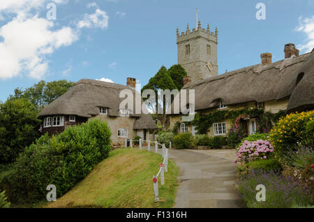 The pretty thatched cottages of Church Hill, with All Saints church in the background. - Stock Photo