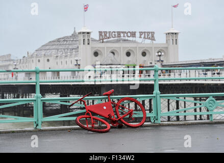 Brighton, UK. 26th August, 2015. UK weather. An abandoned red bicycle on Brighton seafront as high winds and torrential - Stock Photo