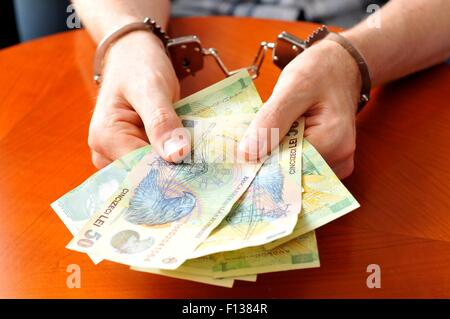 Convict with handcuffs shows pile of money - Stock Photo