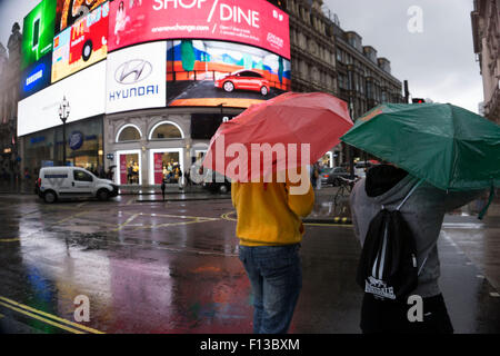 London, UK. Sunday 23rd August 2015. Heavy summer rain showers in the West End. People brave the wet weather armed - Stock Photo