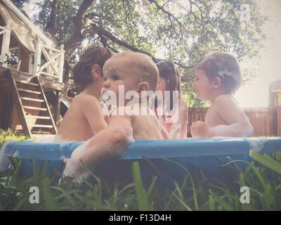 Children bathing and playing in an outdoor bath tub in the garden - Stock Photo