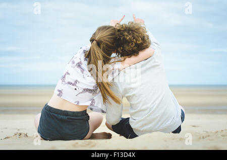 Rear view of teenage boy and girl sitting on beach pointing at sky - Stock Photo