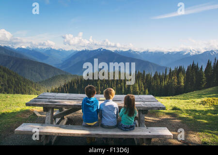 Rear view of three children sitting on a bench in countryside - Stock Photo