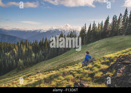 Boy sitting on a rock on a mountain - Stock Photo