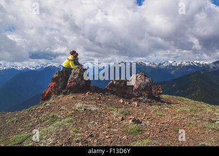 Mother sitting on a rock on mountain hugging her son - Stock Photo