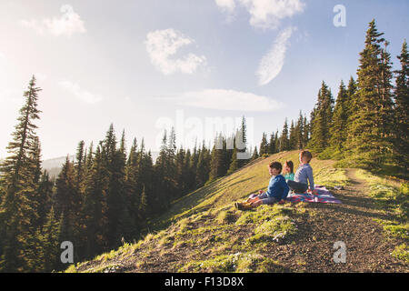 Three children sitting on a mountain - Stock Photo