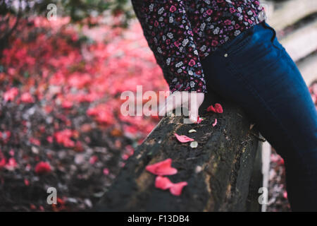 Close-up of mid section of a woman sitting on a wooden fence - Stock Photo