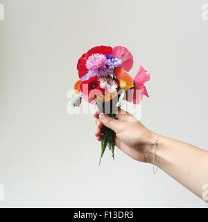woman's hand holding bunch of wildflowers - Stock Photo