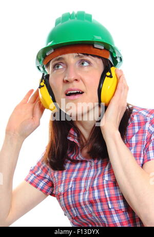 Female construction worker can not hear because wearing green helmet and protective headphones, safety - Stock Photo
