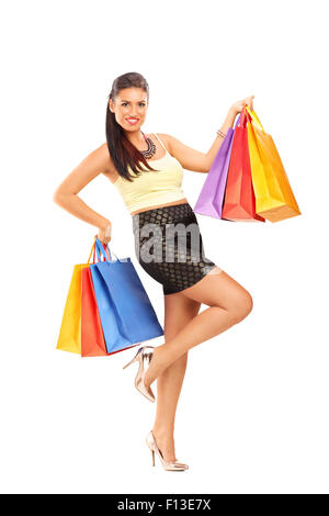 Full length portrait of a beautiful young woman holding few shopping bags and looking at the camera isolated on - Stock Photo