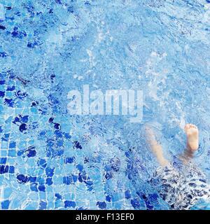 Boy splashing in swimming pool - Stock Photo
