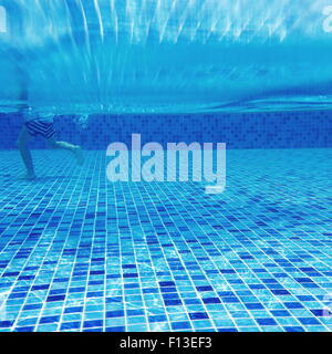Underwater view of a boy walking in a swimming pool - Stock Photo