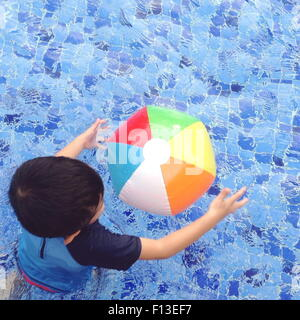 Overhead view of a boy playing with a beach ball in the swimming pool - Stock Photo