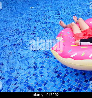 Mature man relaxing on inflatable donut in a swimming pool - Stock Photo