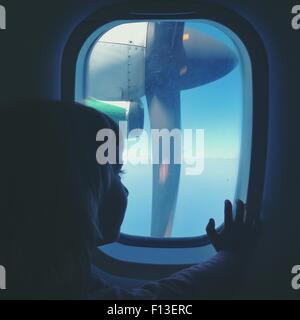Girl sitting on a plane looking through window - Stock Photo