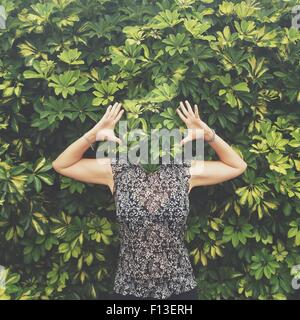Women with face hidden behind leaves standing with raised arms - Stock Photo