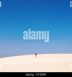 Man walking up a sand dune - Stock Photo