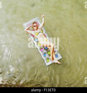 Overhead view of a woman lying on an inflatable mattress in the sea - Stock Photo